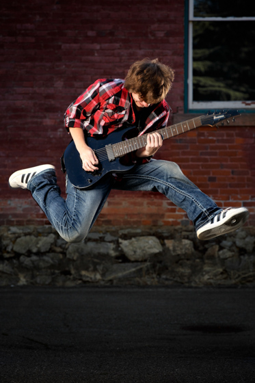 senior portrait jumping with guitar